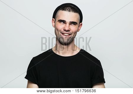 Studio portrait of adult man making smiling face on white background.