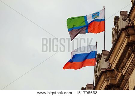 Flags of the Russian Federation and the Belgorod region waving on the parapet of the administrative building of the Soviet Stalinist architecture