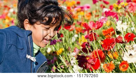 Child is playing in the flower garden in the afternoon