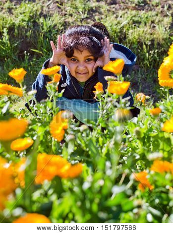 Child in sitting inside the yellow flower garden on afternoon