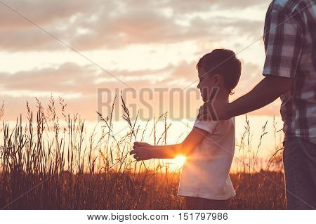 Father and son playing in the park at the day time. People having fun outdoors. Concept of friendly family.