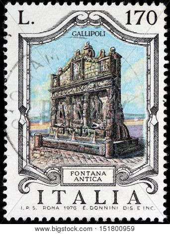LUGA RUSSIA - JUNE 25 2016: A stamp printed by ITALY shows view of The famous Greek Fountain (16th century) in Gallipoli - town and commune in the province of Lecce in Apulia Italy circa 1976