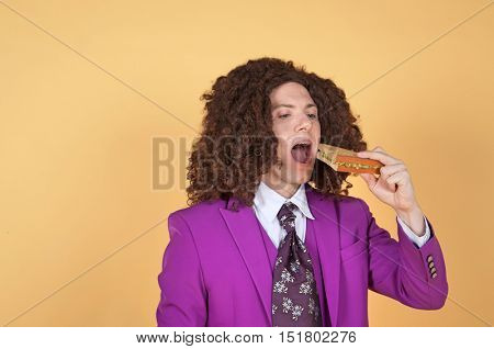 Caucasian man with afro wearing Purple Suit eating sandwich