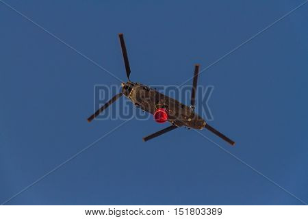 ROME - AUGUST 23: Firefighting twin rotor helicopter carrying bucket containing water from Mediterranean Sea to put out fires on scrubland on August 23 2016 in Rome.