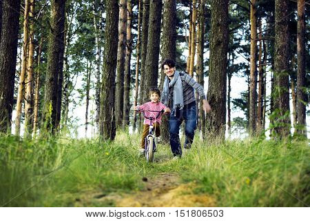 father learning his son to ride on bicycle outside, real happy family in summer forest enjoing nature warm air