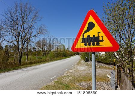 Swedish road sign Level crossing without gates or barriers ahead at the side of a narrow road.