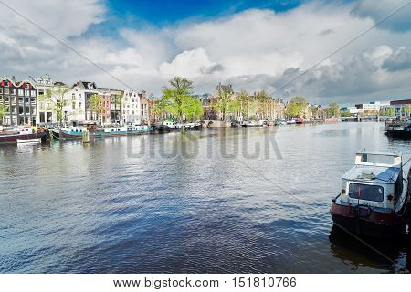 embankment of Amstel canal with traditional houses in Amsterdam, Netherlands