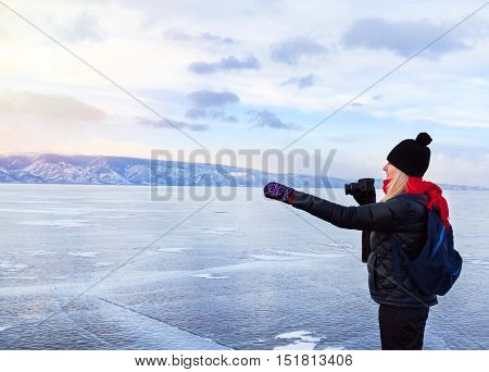 Woman tourist photographer is indicating something outside standing at frozen surface of lake Baikal at sunset. Winter tourism concept.