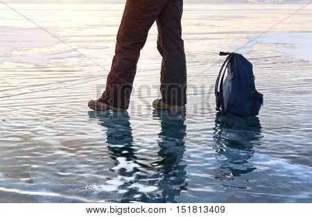 Man foot at ice surface at lake Baikal. Winter activity and travel concept