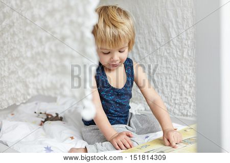 Childhood And Leisure. Adorable Sweet Little Blonde Boy In Sleeping Suit Sitting On His Bed In Front