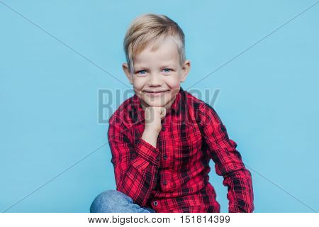 Fashionable little kid with red shirt. Fashion. Style. Studio portrait over blue background