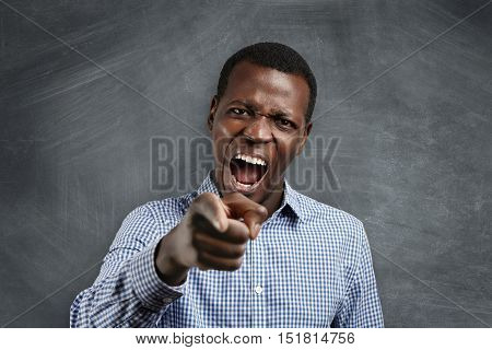 Get Out Of Class! Headshot Of Angry Furious Young Dark-skinned Teacher, Screaming And Pointing At Hi