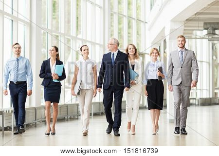 people, work and corporate concept - business team with folders walking along office building and talking