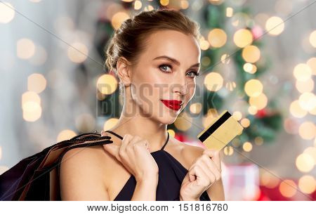 people, luxury, holidays and sale concept - beautiful woman with credit card and shopping bags over christmas tree lights background