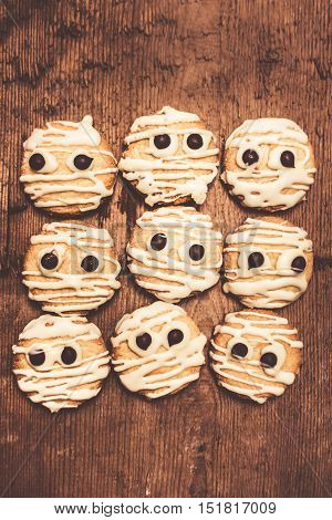 Frightening kitchen foods with mummy white choc short-bread decorations looking fearful on wooden backdrop. Halloween themed food