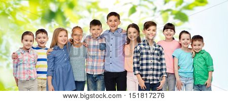 childhood, fashion, friendship and people concept - group of happy smiling children hugging over green natural background