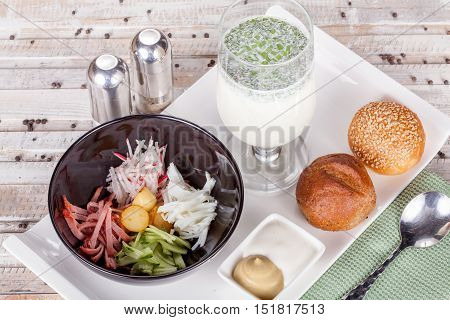 Russian soup Okroshka with bread on white table