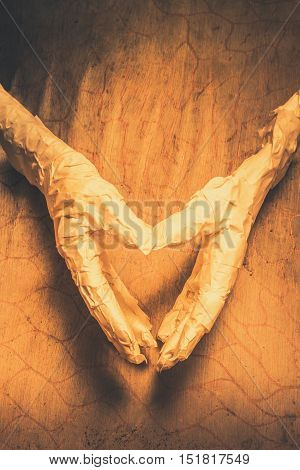 Quirky vintage still death on the hands of a Pharaoh mummy showing love heart sign with bandaged fingers. Halloween love with a mummies day heart