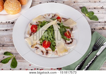 Arugula salad with mushrooms and cheese on white table
