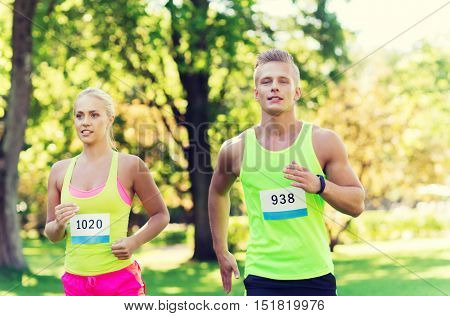 fitness, sport, friendship, race and healthy lifestyle concept - happy teenage friends or sportsmen couple running marathon with badge numbers outdoors