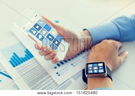 business, technology and people concept - close up of woman hand holding transparent smartphone and smartwatch with application icons on screen at office