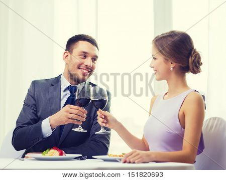 restaurant, couple and holiday concept - smiling couple with main course and red wine at restaurant