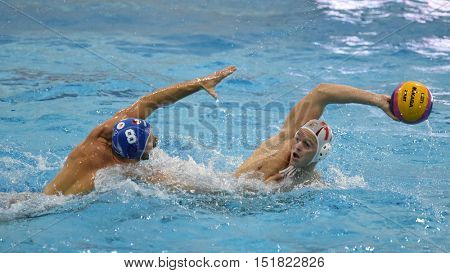 KAPOSVAR, HUNGARY - OCTOBER 5: Norbert Juhasz-Szelei (in white) in action at a Hungarian national championship water-polo game Kaposvar (white) vs Honved (blue) on October 5, 2016 in Kaposvar, Hungary