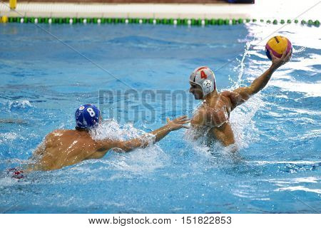 KAPOSVAR, HUNGARY - OCTOBER 5: Samuel Palotas (in white) in action at a Hungarian championship water-polo game between Kaposvar (white) and Honved (blue) on October 5, 2016 in Kaposvar, Hungary