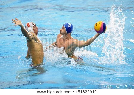 KAPOSVAR, HUNGARY - OCTOBER 5: Tamas Gyarfas (in blue) in action at a Hungarian national championship water-polo game between Kaposvar (white) and Honved (blue) on October 5, 2016 in Kaposvar, Hungary
