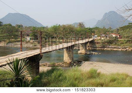VANG VIENG, LAOS - FEBRUARY 18, 2016: Old chain bridge crossing a river in Vang Vieng on February 18, 2016 in Laos, Asia