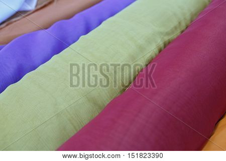 Multi-coloured rolls of a fabric for sewing.