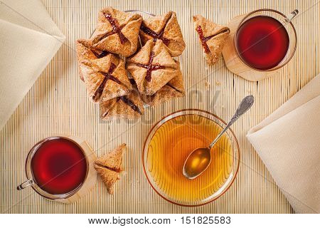 Two cups of black tea, shortcake with jam and honey