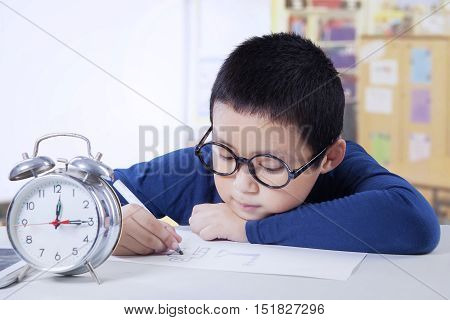 Portrait of a cute boy learning in the classroom with alarm clock on the table and wearing glasses