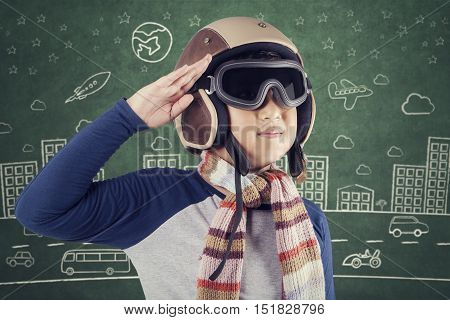Portrait of a male child wearing an aviator helmet and giving respectful gesture with blackboard background