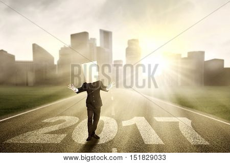 Image of a disoriented businessman walking on the road with number 2017 and cardboard head