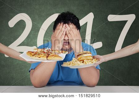 New year resolutions concept. Image of an overweight man closing his eyes in front of junk food with number 2017 on the background