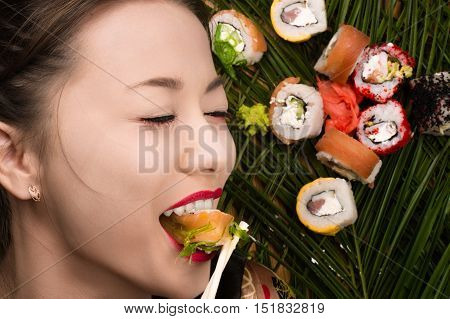 smiling young Korean girl eating sushi rolls