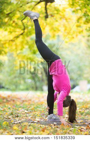 Sporty beautiful young woman practicing yoga, doing standing split pose, urdhva prasarita eka padasana, working out outdoor on autumn day wearing bright sportswear sweatshirt. Full length, side view