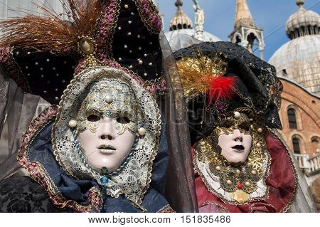 VENICE, ITALY - FEBRUARY 15, 2015: Two models disguised on colorful carnival costumes during the Carnival of Venice