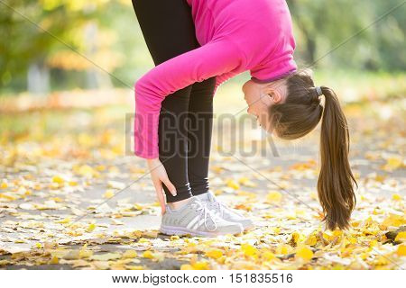 Close-up portrait of sporty beautiful young woman practicing yoga, doing uttanasana intense stretch pose, Standing forward bend or head to knees pose , working out outdoors in autumn park. Side view