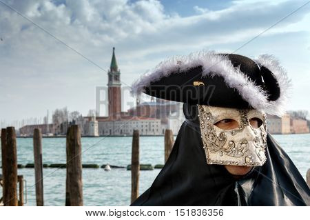 VENICE, ITALY - FEBRUARY 16, 2015: An unidentified person in a black traditional costume, posing at the Grand Canal during the Carnival of Venice
