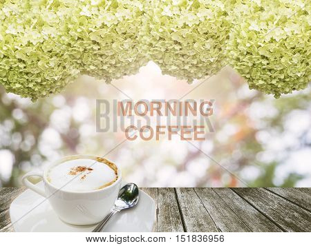 """A white cup of hot coffee on wood plank and flower frame with wording """"morning coffee"""""""