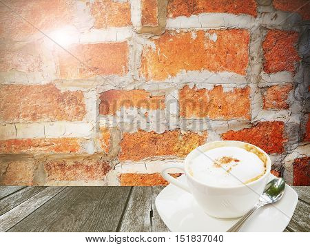 Hot coffee white cup on wppd table and brick wall background
