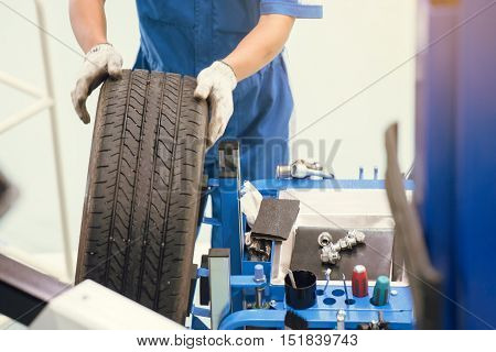 Professional car mechanic changing car wheel in auto repair service.