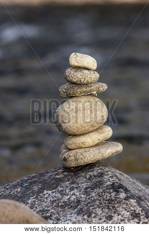Small rock cairn. Small rocks stacked up into a rock cairn on a boulder the the river.