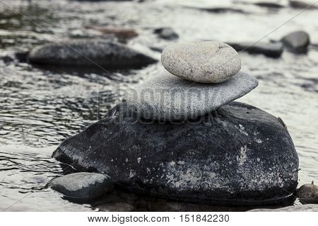 Rock cairn by calm water. Small rocks stacked up into a rock cairn on a boulder the the river.