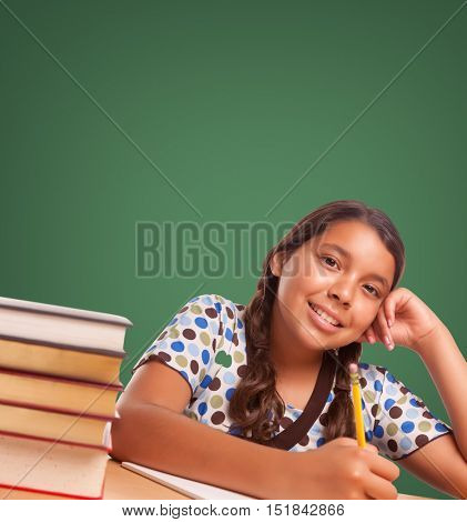 Cute Smiling Hispanic Girl Studying In Front of Blank Chalk Board.