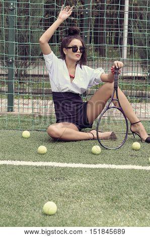 Model Sitting Near The Grid Holding A Tennis Racket