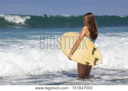 Teenage Girl with a Surfboard at the beach in Southern California.  She is watching the waves and ready to go into the water.