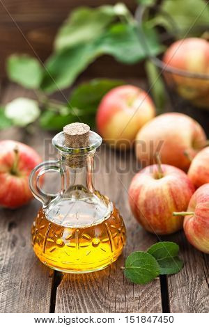 apple cider vinegar in a bottle nad fresh fruits with leaves